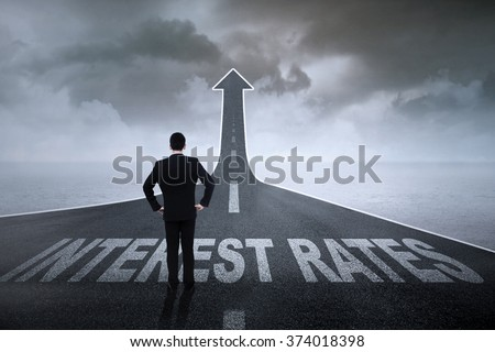 Image of successful entrepreneur standing on the road turning into upward arrow with Interest Rates words on it