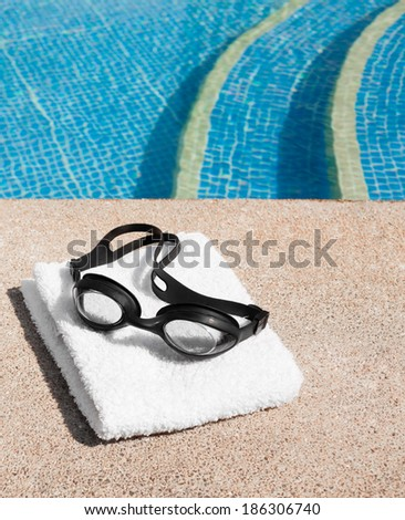 Image of swimming pool, goggles and towel. - stock photo