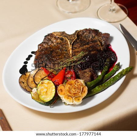 Image of tasty t-bone steak with vegetables in restaurant - stock photo