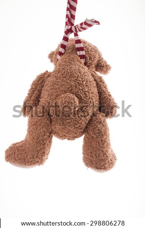 Image of teddy bear who is committing suicide by hanging itself - stock photo