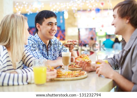 Image of teenage friends interacting in cafe - stock photo