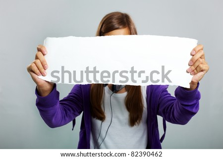 Image of teenage girl in casual clothes holding blank sheet of paper