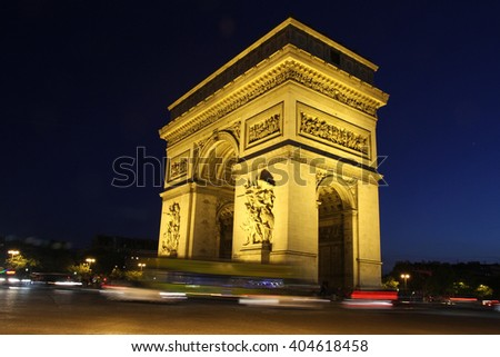 Image of the Arc de Triomphe taken at night. Image is in black and white. Taken in Paris. The movement of passing cars can be seen. Monument is illuminated. - stock photo