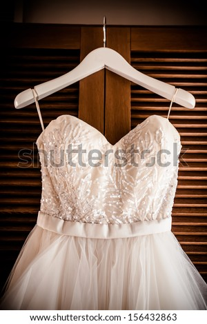 image of the bodice of a weeding dress on a hanger  against a wooden revolving door
