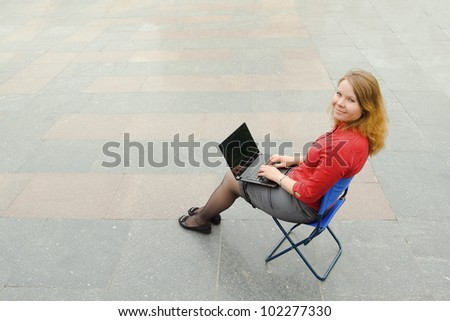 Image of the businesswoman sitting with the laptop and looking at the camera in the empty street. Focus is made on top of the background marbled tile in the street.