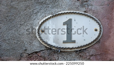 Image of the number 1 (indicating a house number) on weathered stucco wall of antique house. France. - stock photo