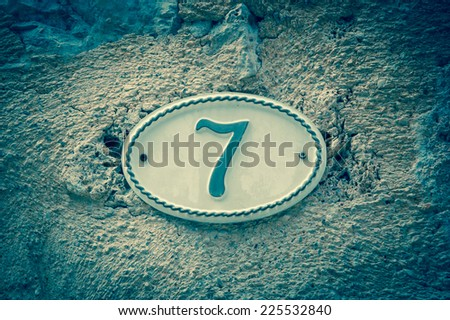 Image of the number 7 (indicating a house number) on weathered stucco wall of antique house. France. Aged photo. - stock photo