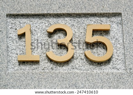 Image of the number 135 on a wall indicating a house number - stock photo