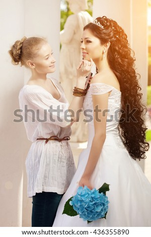 Image of the stylist takes care of the bride - stock photo