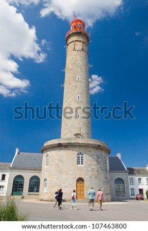 Image of the walking tourists near the Grand lighthouse against the blue sky with clouds. - stock photo