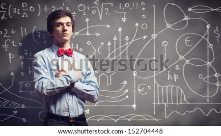 Image of thoughtful male student holding notebook in classroom - stock photo