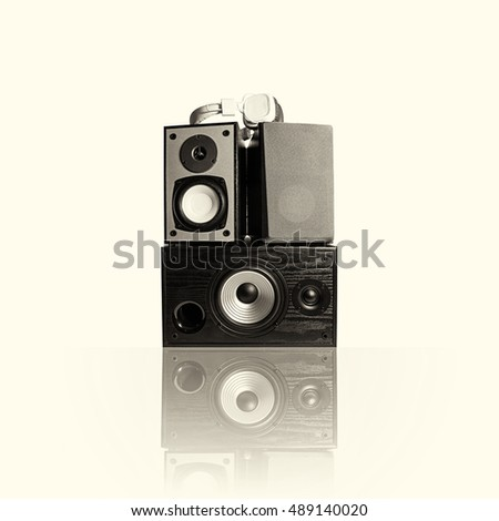 Image of three audio speakers in a wooden case and headphones. Photo black and white, toned, isolated on a light background with reflection. There is an empty seat for your text.