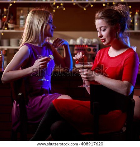 Image of three beautiful friends sitting in cocktail bar - stock photo