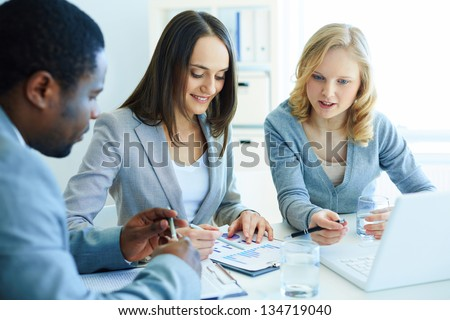 Image of three business partners discussing documents at meeting - stock photo