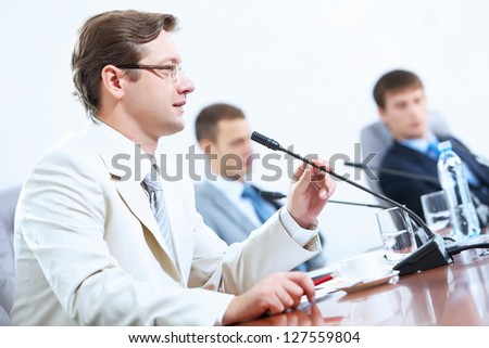 Image of three businesspeople at table at conference - stock photo