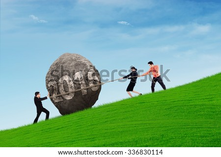 Image of three businesspeople pulling a stone on the hill with numbers 2016 - stock photo