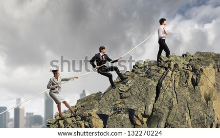Image of three businesspeople pulling rope against city background