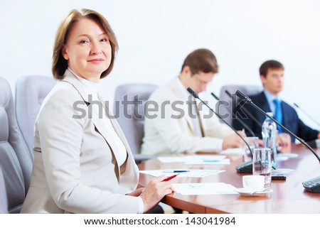 Image of three businesspeople sitting at table at conference - stock photo