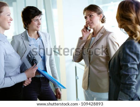 Image of three businesswomen looking at their colleague speaking on the phone