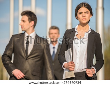 Image of  three confident successful businesspeople in suits at a meeting.