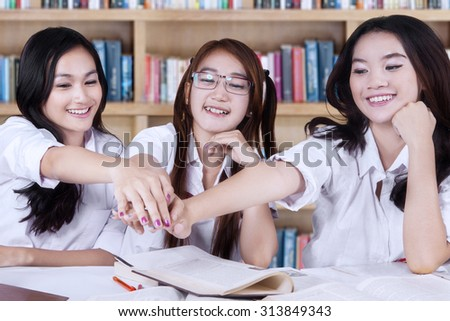Image of three female high school students sitting in the library and joining their hands