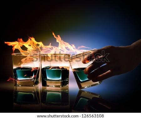 Image of three glasses of burning emerald absinthe - stock photo