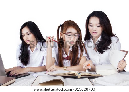 Image of three lovely female students with long hair doing school task together with books and laptop, isolated on white background