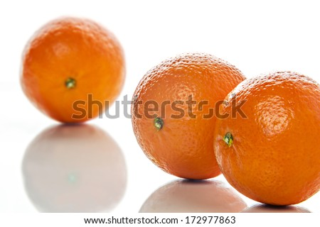 Image of three orange mandarins on white background