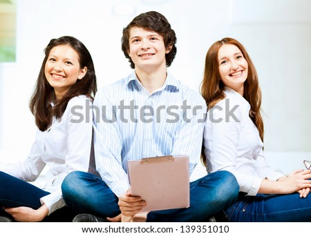 Image of three students in casual wear sitting on floor and smiling