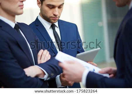 Image of three young businessman using touchpad  - stock photo