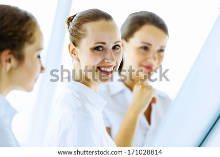 Image of three young businesswomen at meeting
