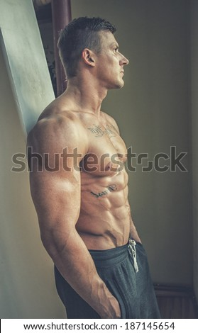 Image of topless man with hands in pockets who is staring in window