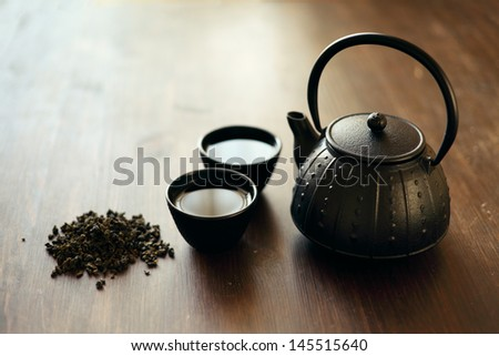Image of traditional eastern teapot and teacups on wooden desk - stock photo