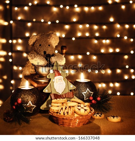 Image of traditional x-mas toys on glowing lights background, Christmastime decorations still life, teddy bear, candles, decorative Christmas tree and homemade cookies on the holiday table - stock photo