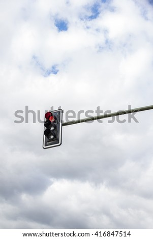 Image of traffic lights while red light on. Cloudy sky background