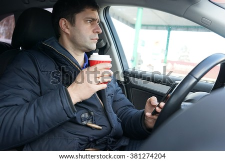 Image of transportation and vehicle concept - man drinking coffee while driving the car                                - stock photo