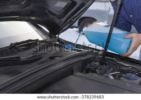 Image of 		transportation, winter, people and vehicle concept - closeup of man pouring washer fluid into car