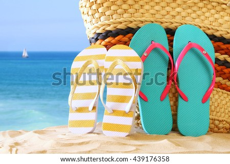 Image of tropical sandy beach, straw bag and flip flops. Summer concept