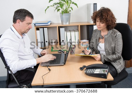 Image of two business partners using laptop at meeting