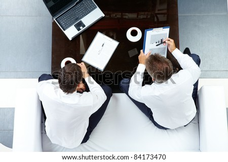 Image of two businessmen discussing work at meeting in office - stock photo