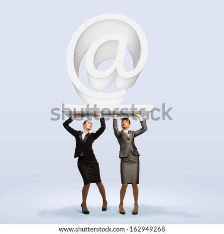 Image of two businesswomen holding at symbol. Partner and cohesion - stock photo