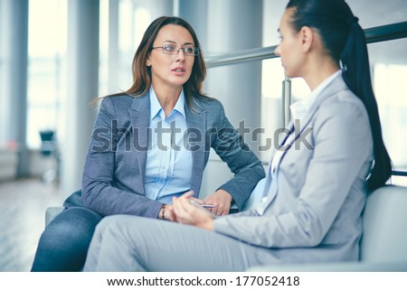 Image of two businesswomen sitting and discussing new ideas - stock photo