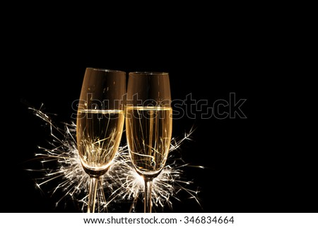 Image of two champagne glasses with burning sparkler on black background - stock photo