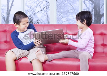 Image of two children sitting on the sofa and fighting to take over laptop computer