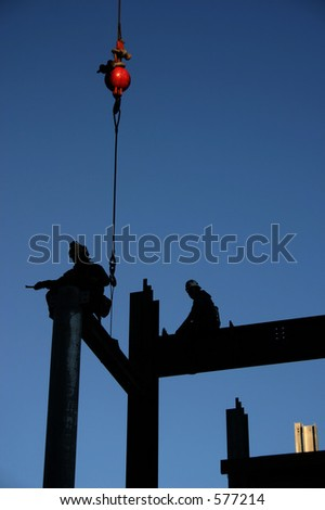 Image of two construction workers directing an i-beam into its final position. The red weight of the crane is the only color element in this image except for the sky. Image is not retouched. - stock photo