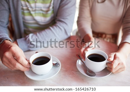 Image of two cups of coffee held by hands of dates
