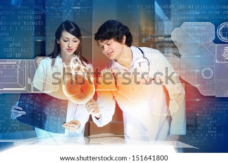 Image of two doctors cardiologist examining virtual heart - stock photo