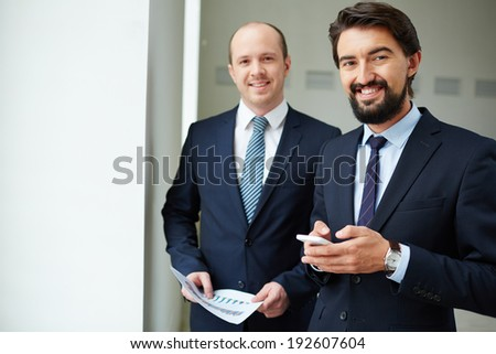 Image of two elegant businessmen looking at camera in office - stock photo