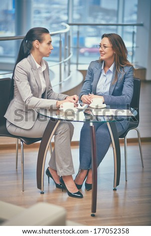 Image of two friendly businesswomen talking by the cup of coffee in office - stock photo