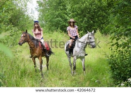 Image of two girls ride horses in the park